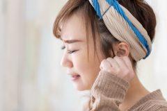 頭痛とめまいを感じる女性